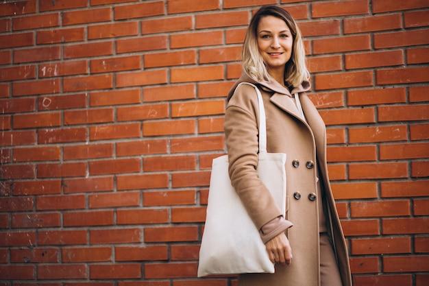 Jovem mulher com saco pela parede de tijolo