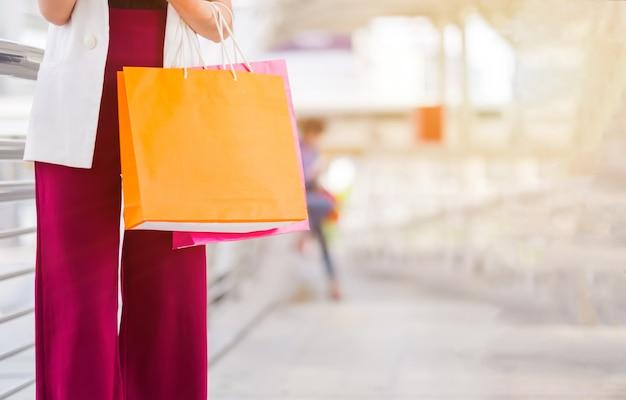 Jovem mulher com sacola colorida.