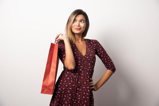 Jovem mulher com sacola de compras na parede branca.