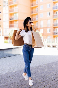 Jovem mulher com sacolas de compras e sorvete na rua da cidade