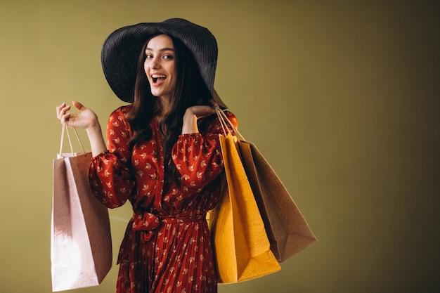 Jovem mulher com sacolas de compras em um lindo vestido e chapéu