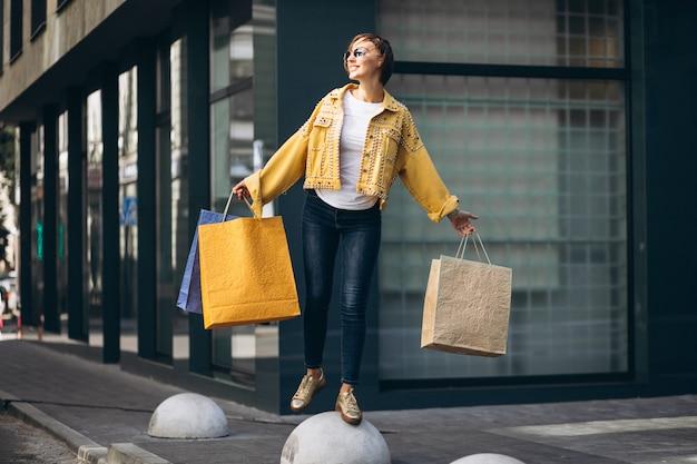 Jovem mulher com sacolas de compras na cidade
