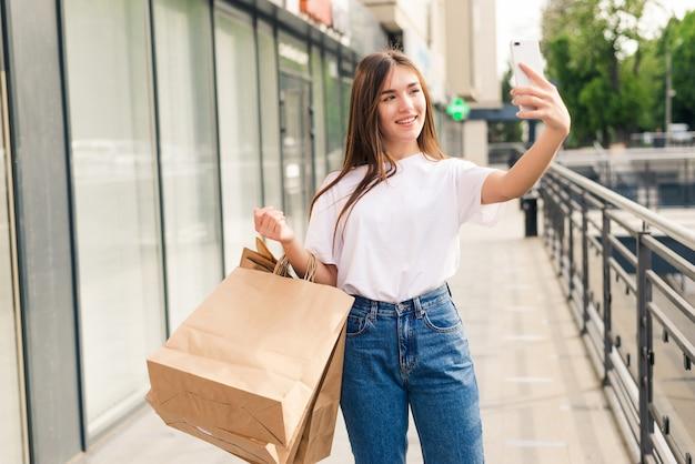 Jovem mulher com sacolas de compras tirando uma selfie com o celular ao ar livre