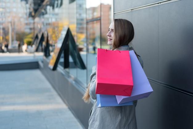 Jovem mulher com sacos coloridos na rua.