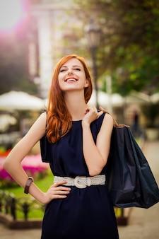 Jovem mulher com sacos de compras, andando na rua da cidade