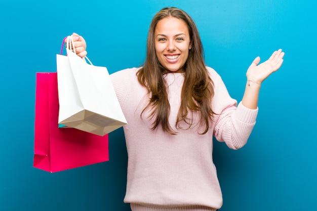 Jovem mulher com sacos de compras contra o fundo azul