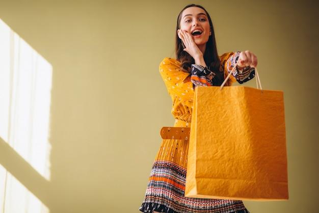 Jovem mulher com sacos de compras em um lindo vestido