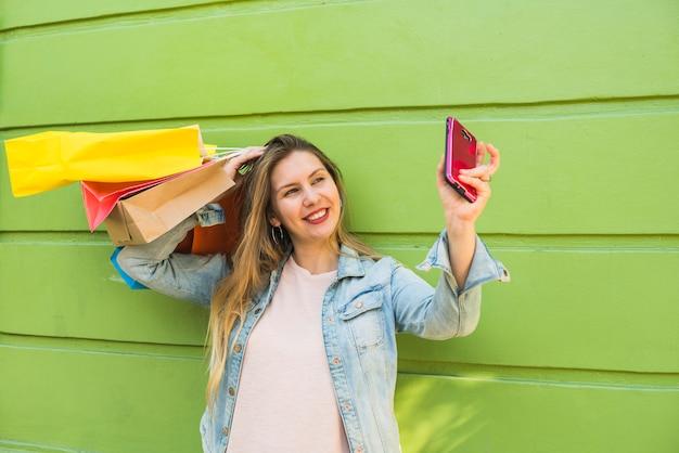 Jovem mulher com sacos de compras, tendo selfie