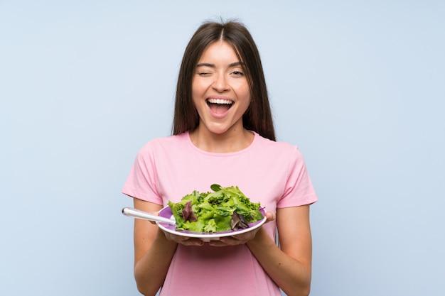 Jovem mulher com salada isolado parede azul