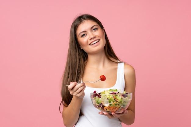 Jovem mulher com salada isolado parede rosa