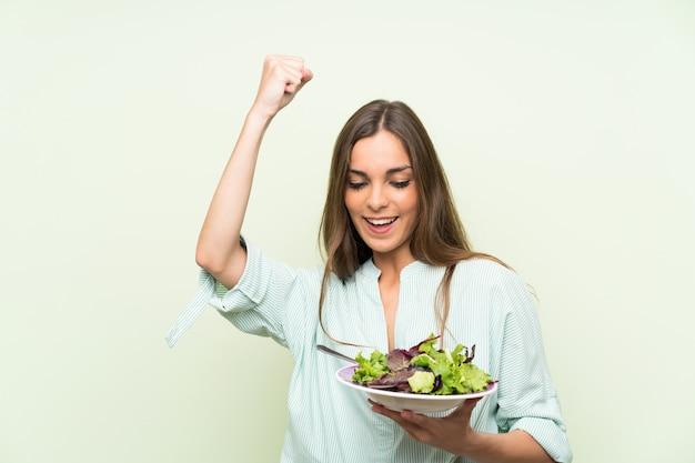 Jovem mulher com salada isolado parede verde comemorando uma vitória