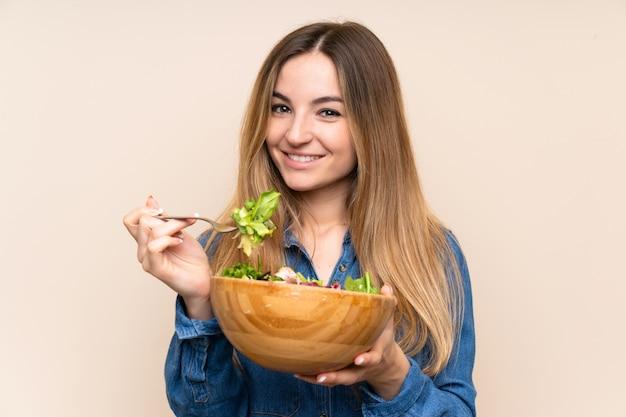 Jovem mulher com salada sobre fundo isolado