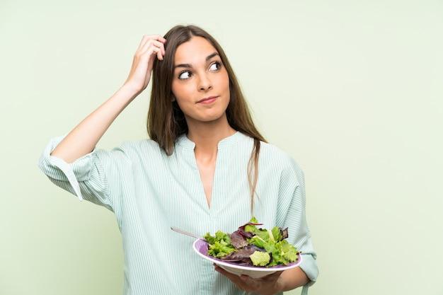 Jovem mulher com salada sobre parede verde isolada, tendo dúvidas e com a expressão do rosto confuso