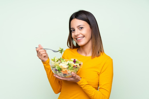 Jovem mulher com salada sobre parede verde isolada