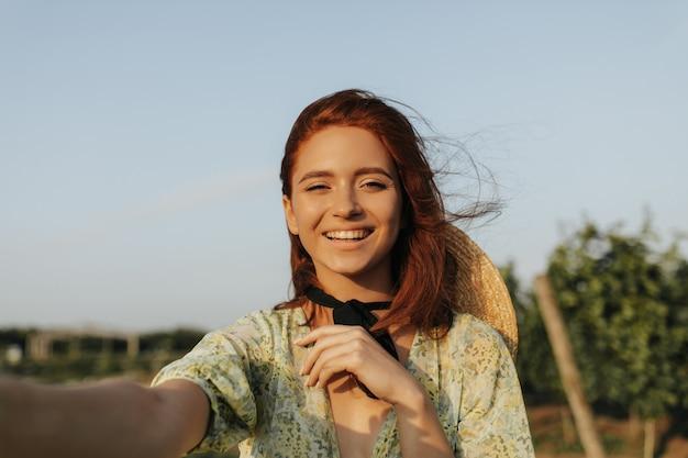Jovem mulher com sardas, cabelo ruivo e bandagem preta no pescoço em roupas verdes estampadas sorrindo e tirando foto ao ar livre