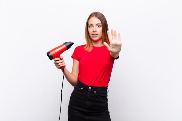Jovem mulher com secador de cabelo olhando sério e com raiva mostrando a palma da mão aberta, fazendo o gesto de parada