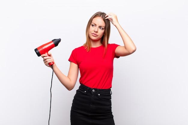 Jovem mulher com secador de cabelo, sentindo-se confuso e confuso