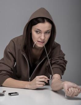 Jovem mulher com seringa e drogas.