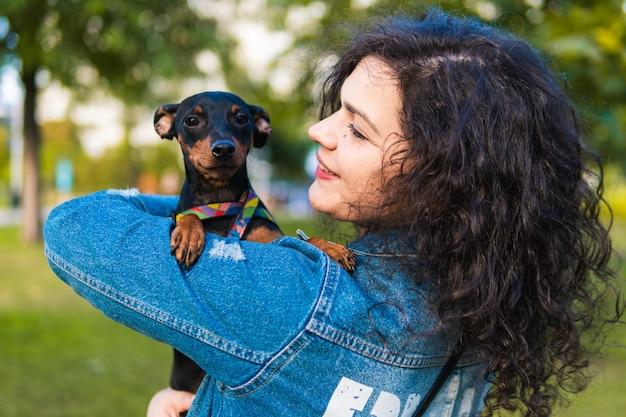 Jovem mulher com seu cachorrinho ao ar livre. cadela pinscher miniatura preta e castanha com o dono em um parque