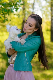 Jovem mulher com seu cachorro. cachorro branco com seu dono. conceito sobre amizade, animal e liberdade.