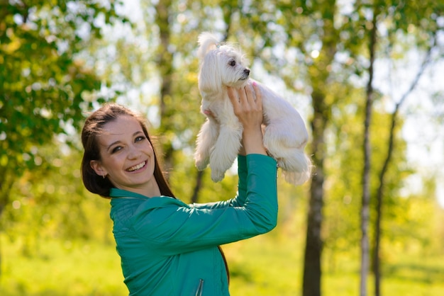 Jovem mulher com seu cachorro. cachorro branco está correndo com seu dono. conceito sobre amizade e animais.