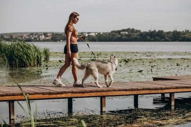 Jovem mulher com seu cachorro husky à beira do lago