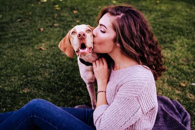 Jovem mulher com seu cachorro no parque. ela está beijando o cachorro