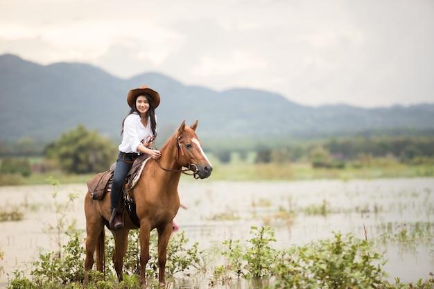 Jovem mulher com seu cavalo na luz do sol de noite. ao ar livre