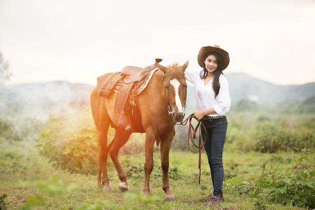 Jovem mulher com seu cavalo na luz do sol de noite.