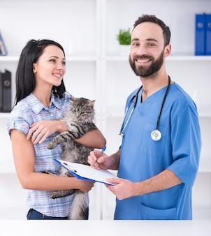 Jovem mulher com seu gato em uma visita ao veterinário.