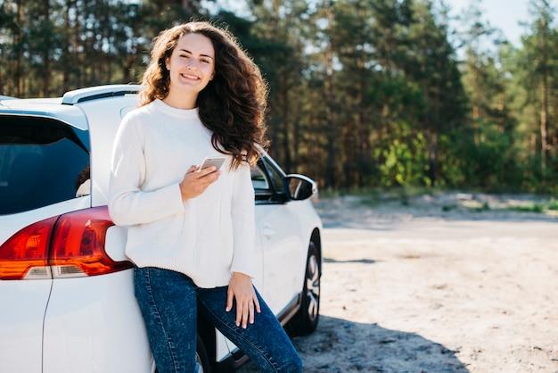 Jovem mulher com smartphone ao lado de seu carro
