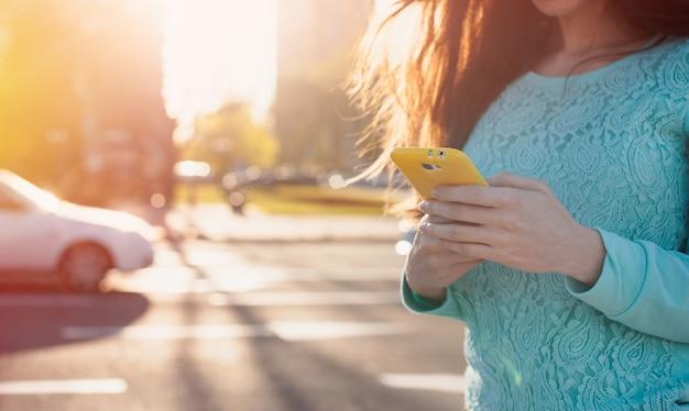 Jovem mulher com smartphone escreve