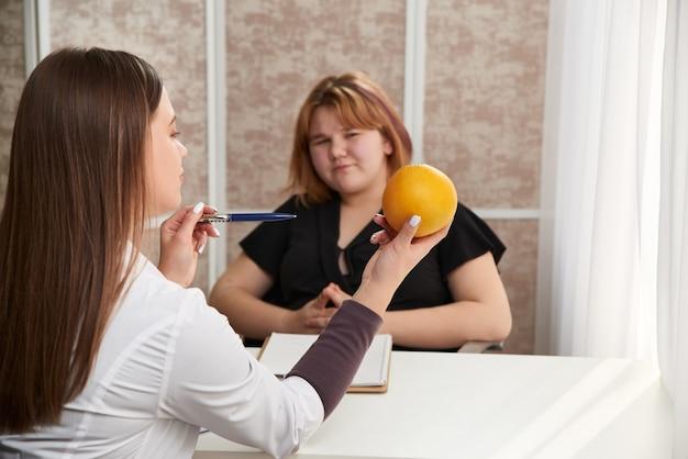 Jovem mulher com sobrepeso visitando nutricionista para perder peso com ajuda de dieta.