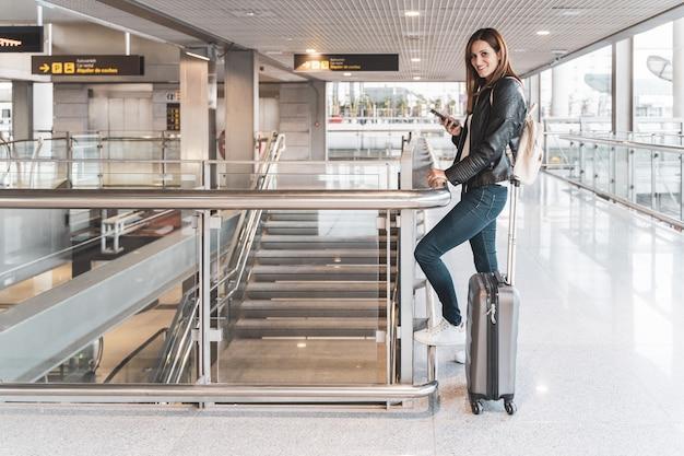 Jovem mulher com sua bagagem e telefone celular esperando no aeroporto. conceito de viagens e férias.