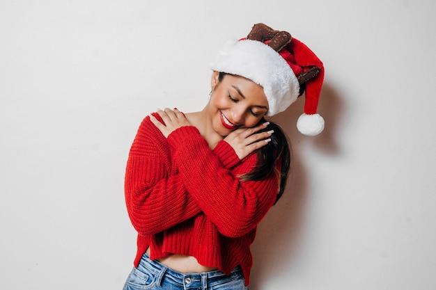 Jovem mulher com suéter casual abraçando a si mesma feliz e positiva, sorrindo confiante. conceito de amor próprio.