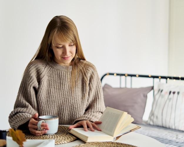 Jovem mulher com suéter lendo livro com uma xícara de chá quente na vida lenta do quarto