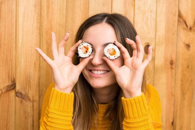 Jovem mulher com sushi sobre parede de madeira