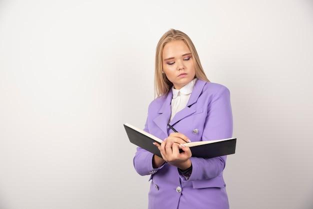 Jovem mulher com tablet aberto na parede branca.
