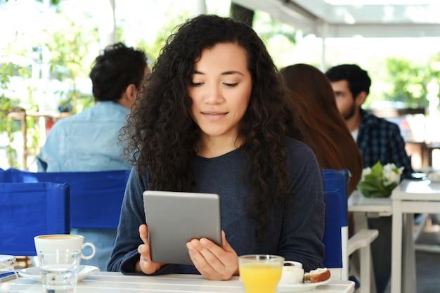 Jovem mulher com tablet na cafeteria.