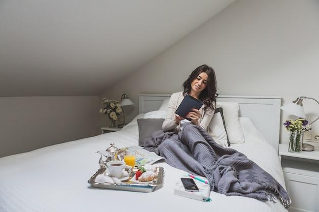 Jovem mulher com tablet sentado na cama