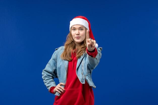 Jovem mulher com tampa vermelha de natal e fundo azul com emoção de natal