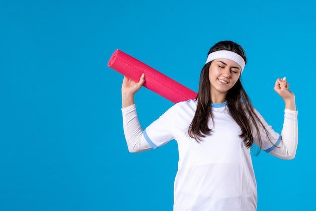 Jovem mulher com tapete de ioga na parede azul de frente