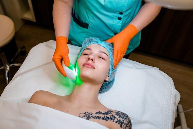 Jovem mulher com tatuagem recebendo tratamento a laser de depilação no rosto no centro de beleza.