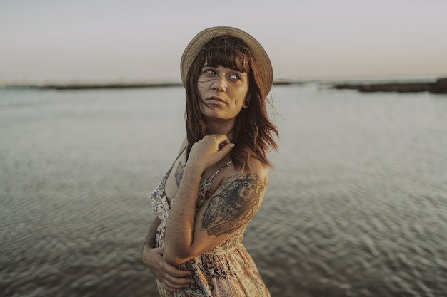 Jovem mulher com tatuagens usando um vestido e chapéu de palha na praia
