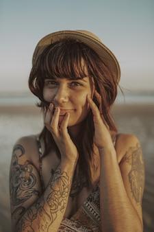 Jovem mulher com tatuagens, vestido e chapéu de palha no oceano turva