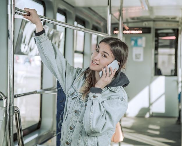 Jovem mulher com telefone em transportes públicos.