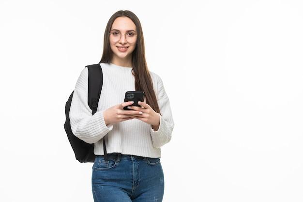 Jovem mulher com telefone inteligente com mochila na parede branca