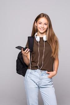Jovem mulher com telefone inteligente ouve música com mochila isolada na parede branca