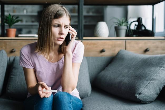 Jovem mulher com termômetro falando no celular