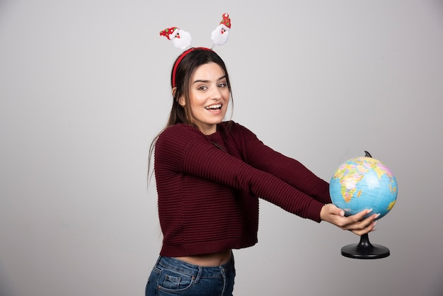Jovem mulher com tiara de natal segurando um globo terrestre.